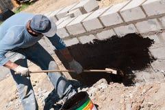 Man tarring a house foundation stock photos