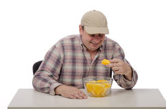 A man tastes a juicy yellow watermelon. Middle aged man in a baseball cap tastes juicy yellow watermelon Stock Photo