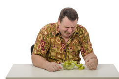Man tastes the sour grapes. A man in a colored shirt tastes sour grapes Royalty Free Stock Photography