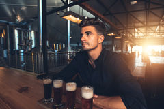 Man tasting different types of beer at the brewery. Young man tasting different types of beer at the brewery factory. Four different varieties of craft beer on a Stock Photos