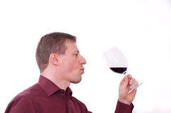 Man is tasting and holding a glass of red wine. A man is tasting a red wine Royalty Free Stock Photography