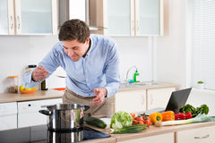 Man Tasting Meal In Kitchen Stock Photo