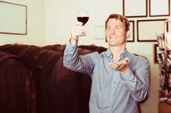 Man tasting wine before purchasing it in winery. Adult man tasting wine before purchasing it in winery Stock Photo