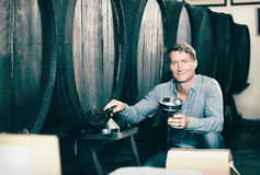 Man tasting wine before purchasing it in winery. Portrait of positive man tasting wine before purchasing it in winery royalty free stock photos