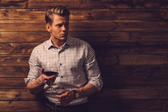 Man tasting wine in rural cottage interior.  Royalty Free Stock Photography
