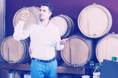 Man tasting wine in store. Smiling man tasting glass of hard liquor in alcohol section in store Royalty Free Stock Images