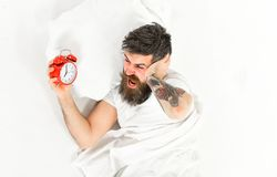 Man with tattoo and beard having trouble waking up. With alarm clock, white background. Man with shouting face suffer of alarm stock image