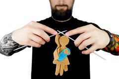 Man with tattoo and beard holding knitted needles with knitted silhouette of female and male. Strict brutal man with tattoo and beard in black t-shirt holding Royalty Free Stock Photos