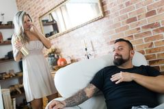 Man with tattoo sitting in armchair and woman having golden bottle of champagne in background stock photos