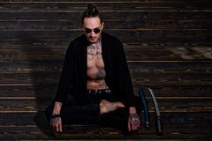Man with tattooed torso sitting in meditation pose with swords. Man with tattooed torso in black clothes sitting in meditation pose with swords on wooden floor stock photography