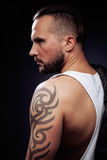 A man with tattooes on his arms. Silhouette of muscular body. caucasian brutal hipster guy with modern haircut, looking. Like criminal close up Stock Photo