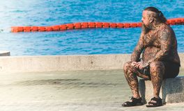 Man With Tattoos Sitting on Gray Concrete Floor Near Body of Water royalty free stock images