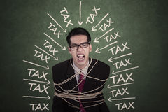 Man with tax problems bound by rope Stock Photos