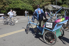 Man on taxi bike waits for clients in central park new york Royalty Free Stock Photography