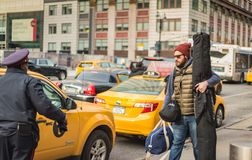 Man at Taxi Loading - Penn Station - New York, NY. Man carrying skis and travel gear to taxi from Penn Station in New York City Royalty Free Stock Photography