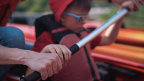 Man teach son how to row in kayak with oars. Father show to son in kayak how to row with oars in kayak Stock Image