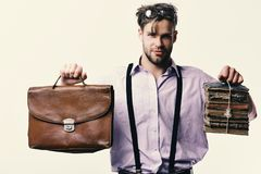 Man or teacher with bristle, glasses and confident face. Wisehead syndrome and hard work concept. Nerd or bookworm. Wearing suspenders. Man with briefcase and stock photo