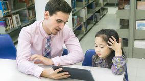 Man teacher and kid student learning and looking on tablet devic. The men teacher and kid student learning and looking on tablet device with self book in the Royalty Free Stock Photography