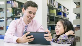 Man teacher and kid student learning and looking on tablet device Royalty Free Stock Image