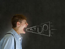 Angry man shouting stop through chalk megaphone blackboard background Stock Image