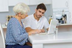 Man teaches elderly woman how to work using laptop Stock Photos