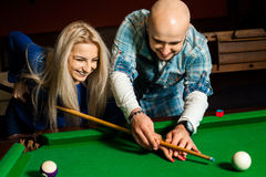 Man teaches his girlfriend how to play on the pool table Stock Image