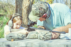 Man teaches little girl how to shoot Stock Photography