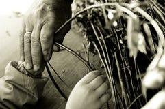 Man teaching child making a wicker basket Royalty Free Stock Image