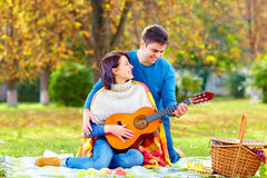 Man teaching girl play a guitar on autumn picnic Royalty Free Stock Photos
