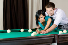 Man teaching girl to play billiards Stock Images