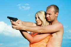Man is teaching girlfriend to shoot. Royalty Free Stock Photos