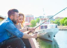 Man teaching his girlfriend to fishing. Date, love and hobby concept. Man teaching his girlfriend to fishing. Couple with rod in harbor. Date, love and hobby stock photos