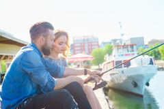 Man teaching his girlfriend to fishing. Date, love and hobby concept. Man teaching his girlfriend to fishing. Couple with rod in harbor. Date, love and hobby stock image