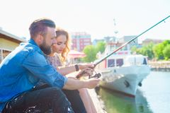 Man teaching his girlfriend to fishing. Date, love and hobby concept. Man teaching his girlfriend to fishing. Couple with rod in harbor. Date, love and hobby stock photography