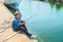 Man teaching his girlfriend to fishing. Date, love and hobby concept. Man teaching his girlfriend to fishing. Couple with rod in harbor. Date, love and hobby royalty free stock photography