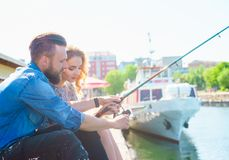 Man teaching his girlfriend to fishing. Date, love and hobby concept. Man teaching his girlfriend to fishing. Couple with rod in harbor. Date, love and hobby royalty free stock images