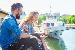 Man teaching his girlfriend to fishing. Date, love and hobby concept. Man teaching his girlfriend to fishing. Couple with rod in harbor. Date, love and hobby royalty free stock image