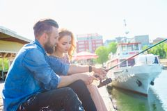 Man teaching his girlfriend to fishing. Date, love and hobby concept. Man teaching his girlfriend to fishing. Couple with rod in harbor. Date, love and hobby royalty free stock photo