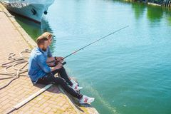 Man teaching his girlfriend to fishing. Date, love and hobby concept. Man teaching his girlfriend to fishing. Couple with rod in harbor. Date, love and hobby stock photo