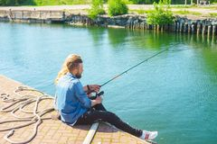Man teaching his girlfriend to fishing. Date, love and hobby concept. Man teaching his girlfriend to fishing. Couple with rod in harbor. Date, love and hobby royalty free stock photos