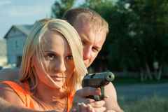 Man is teaching his girlfriend to shoot. Royalty Free Stock Images