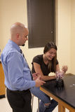 Man teaching science to a female student. A bald male teacher demonstrates the science behind a plasma ball to a young female student Stock Photography