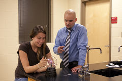 Man teaching science to a female student. A bald male teacher demonstrates the science behind a plasma ball to a young female student Royalty Free Stock Images