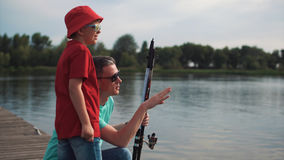 Man teaching son how to fish. Side view of father with son on pier holding rod and teaching how to fish Royalty Free Stock Photo