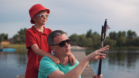 Man teaching son to fish. Side view of men holding rod and explaining son how to fish on background of lake Royalty Free Stock Photos