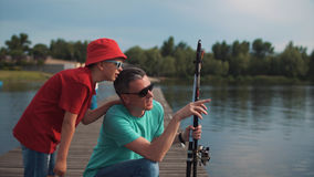 Man teaching son to fish. Side view of men holding rod and explaining son how to fish on background of lake Royalty Free Stock Images