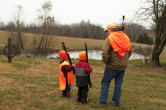 Man teaching sons how to deer hunt. Father teaching sons to hunt and use guns safely stock image