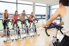 Man teaching spinning class to four people Stock Photography