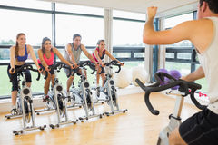 Man teaching spinning class to four people. Spinning exercise bikes in a bright gym room Cropped men teaching spinning class to four people in gym Royalty Free Stock Photo
