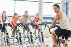 Man teaching spinning class to four people Royalty Free Stock Photography